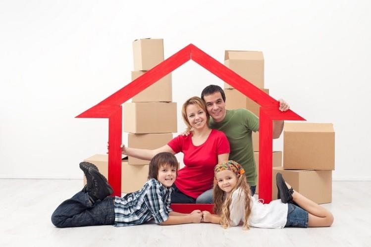 счастливая семья в макете дома на фоне картонных коробок